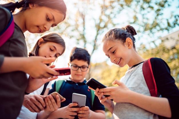 Enfants Jouant à Des Jeux Vidéo Sur Un Téléphone Intelligent Après L'école Photo Premium