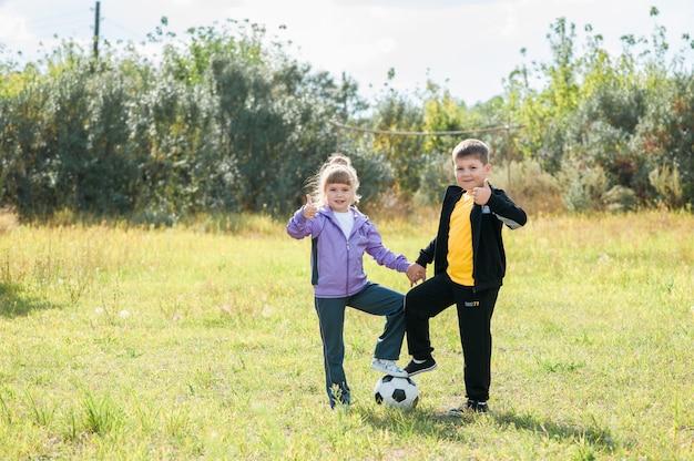 Les enfants jouent au ballon de football sur le terrain. vêtu de vêtements de sport Photo Premium