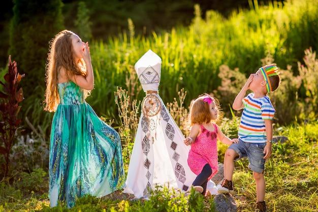 Les enfants jouent comme les autochtones américains sur l'herbe verte dans le domaine Photo gratuit
