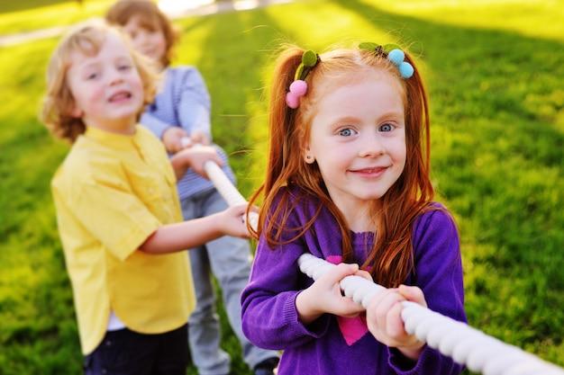 Des enfants jouent à la corde dans le parc. Photo Premium
