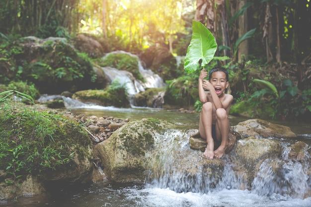 Les enfants jouent joyeusement dans le ruisseau Photo gratuit