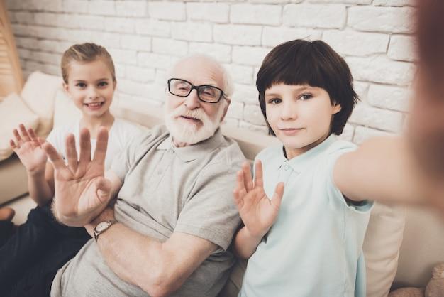 Les enfants et leur grand-père font un appel vidéo en agitant les mains. Photo Premium