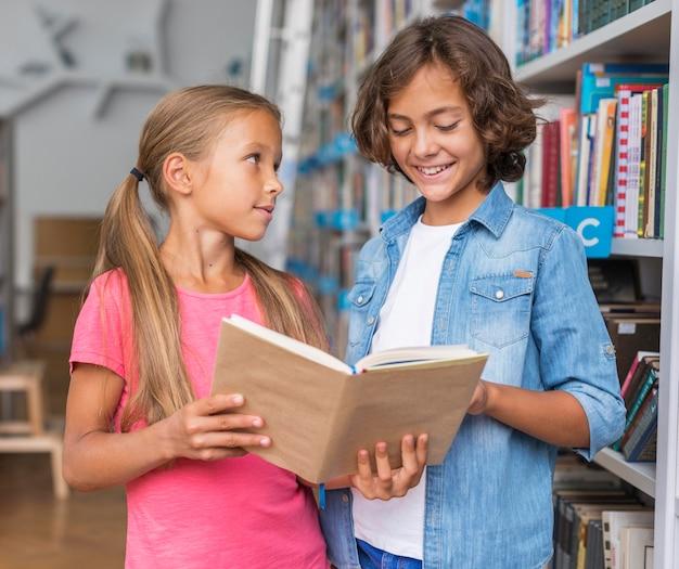 Enfants Lisant Un Livre Dans La Bibliothèque Photo gratuit