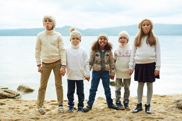 Enfants Ludiques Posant Au Bord Du Lac Photo gratuit