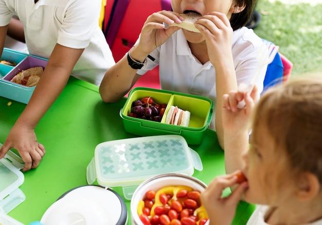 Enfants mangeant à l'école primaire Photo Premium