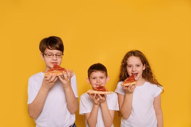 Enfants Mangeant De La Pizza Au Poivre Sur Un Mur Jaune. Photo Premium