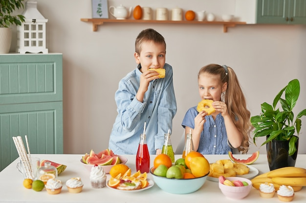 Les Enfants Mangent Des Fruits Sur Une Table Pleine De Nourriture Photo Premium