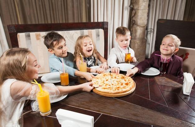 Les Enfants Mangent Une Pizza Au Restaurant. Photo Premium