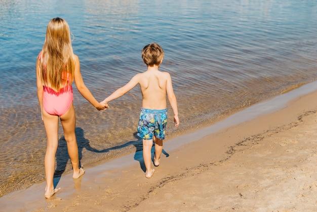 Enfants marchant le long de la côte Photo gratuit