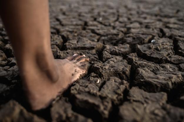 Les enfants marchent pieds nus dans la boue Photo gratuit