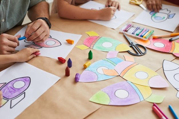 Enfants Méconnaissables Dessinant Des Images De Fusées Spatiales Tout En Profitant D'un Cours D'art à L'école Maternelle Ou Dans Un Centre De Développement Photo Premium