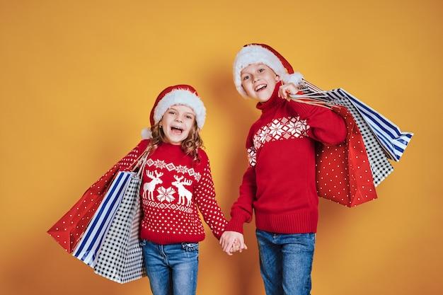 Enfants mignons en chapeaux et chandails de père noël rouge étreignant et tenant des sacs à provisions et ballons dorés sur fond jaune Photo Premium