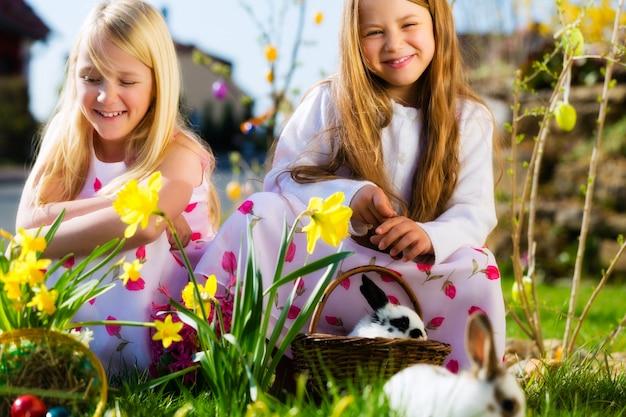 Enfants sur un oeuf de pâques avec un lapin Photo Premium