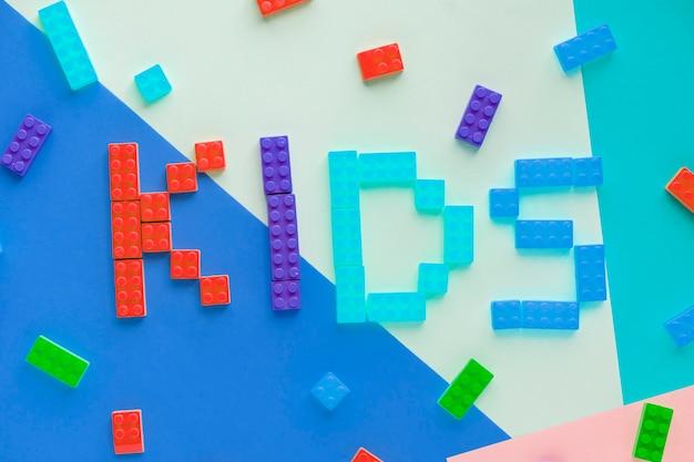 Enfants orthographié mot avec fond de blocs en plastique Photo gratuit