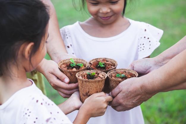 Enfants et parents tenant des jeunes plants dans des pots de fibres recyclés Photo Premium