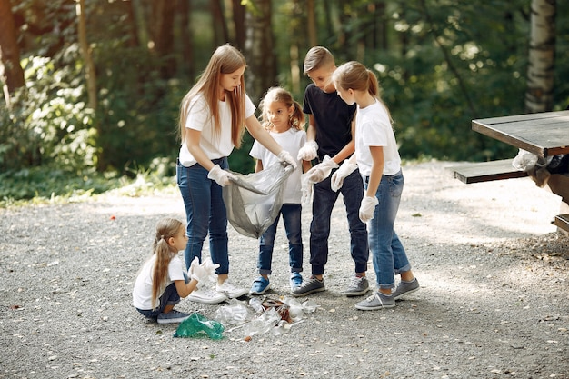Enfants Ramassent Les Ordures Dans Des Sacs à Ordures Dans Le Parc Photo gratuit
