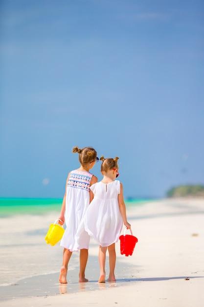 Enfants s'amusant sur une plage tropicale jouant ensemble à l'eau peu profonde Photo Premium