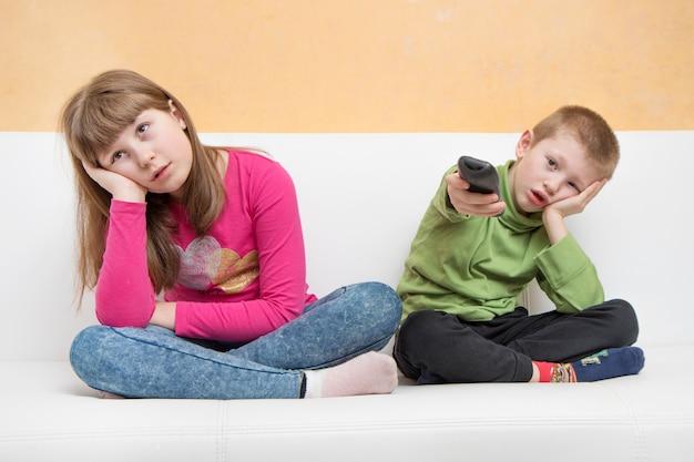 Les Enfants S'ennuient Assis Sur Le Canapé à Regarder La Télévision Pendant La Quarantaine Des Coronavirus Photo Premium