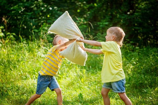 Enfants se battre avec des oreillers dans un jardin d'été ensoleillé Photo Premium