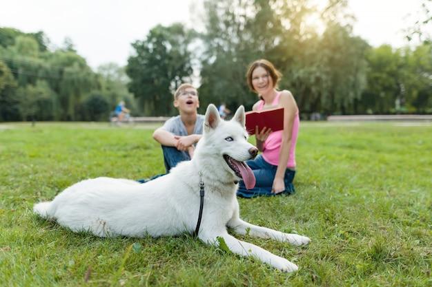 Les enfants se reposent dans le parc avec un chien Photo Premium