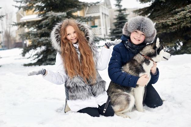 Les enfants sont assis dans la neige et caressaient le chien husky Photo Premium