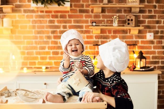 Les enfants sont cuits et jouent avec de la farine et de la pâte dans la cuisine Photo Premium