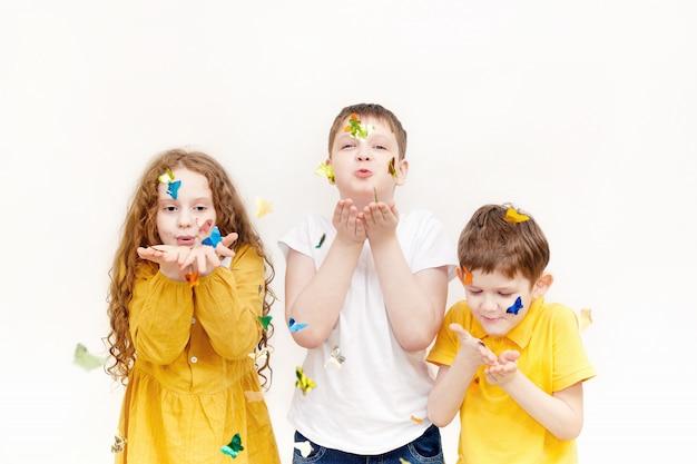 Enfants soufflant des confettis sur fond clair. Photo Premium