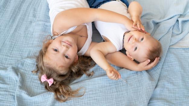 Enfants Souriants à Angle élevé Assis Dans Un Lit Photo gratuit