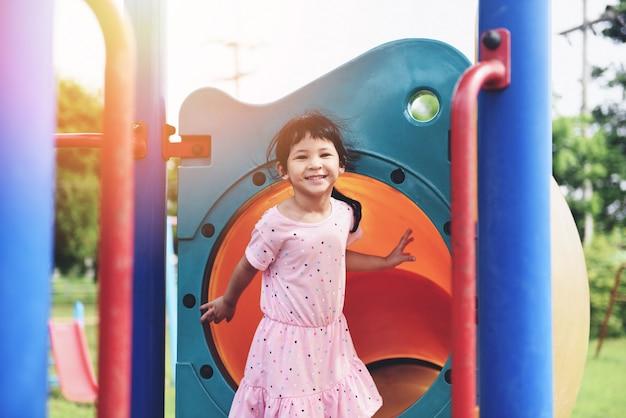 Enfants, sourire, amusement, petite fille, jouer dehors, heureux, dans, les, parc jardin, assis, les, cour de récréation, enfants asiatiques journée internationale des enfants beau mignon Photo Premium