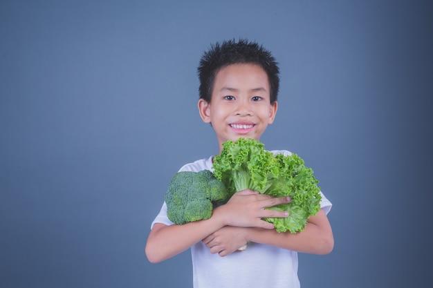 Enfants tenant des légumes sur un fond gris. Photo gratuit