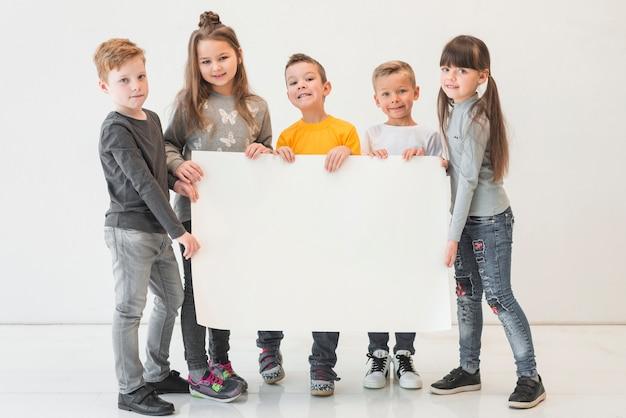 Enfants tenant une pancarte blanche Photo gratuit