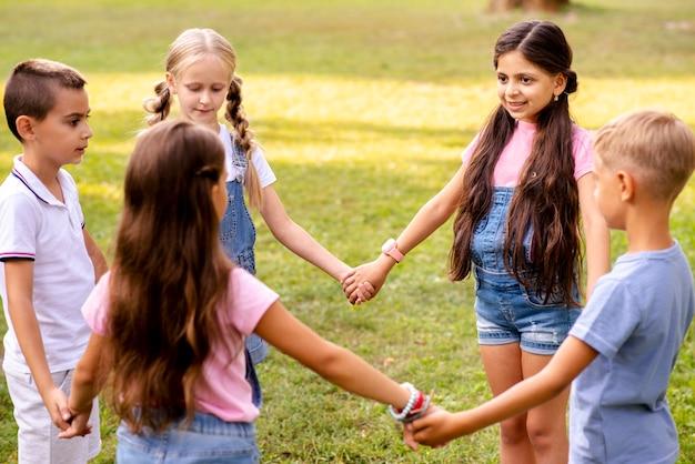 Enfants Tenant Par La Main Forme Un Cercle Photo gratuit