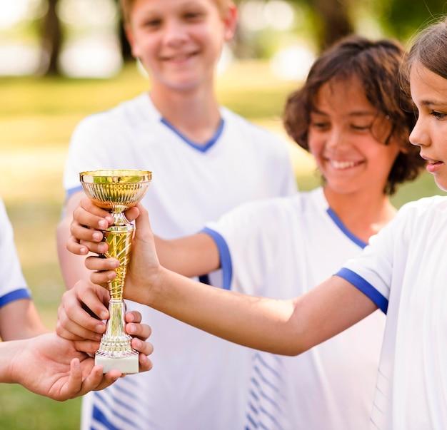 Enfants Tenant Un Trophée D'or Photo gratuit