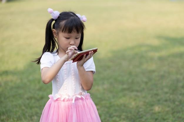 Des enfants thaïlandais debout regardent des films de dessins animés sur un smartphone équipés du système haute vitesse 4g wi-fi dans le jardin du groenland Photo Premium