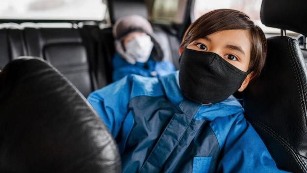 Enfants Tir Moyen Portant Des Masques En Voiture Photo gratuit