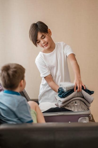 Enfants De Tir Moyen Avec Des Vêtements Pliés Photo gratuit