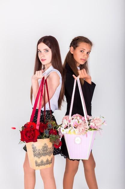 Enfants en uniforme scolaire avec des fleurs. enfance, concept floral Photo Premium
