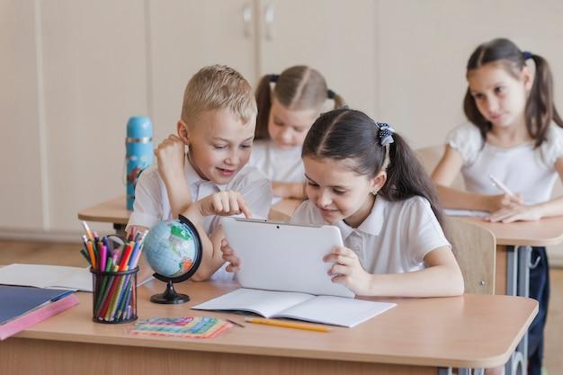 Enfants utilisant une tablette pendant la leçon Photo gratuit