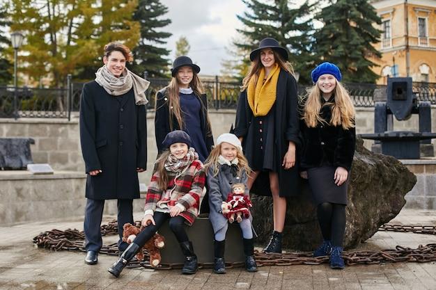 Les enfants avec des valises voyagent, des vêtements de printemps automne rétro. Photo Premium