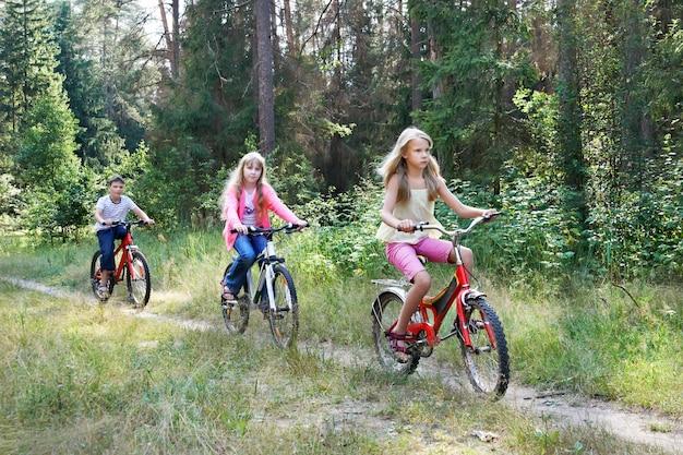 Enfants à Vélo Dans Les Bois Photo Premium