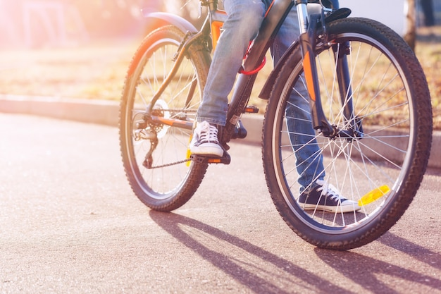 Enfants à vélo sur la route goudronnée en début de journée d'été. Photo Premium