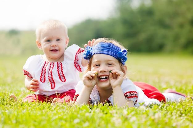 Enfants en vêtements folkloriques sur l'herbe Photo gratuit