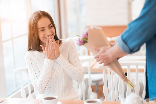 Engagement surprise dans cafe man gives flowers. Photo Premium