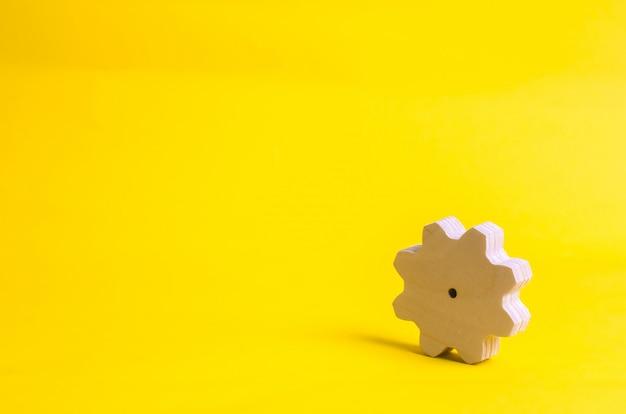 Un engrenage en bois sur un fond jaune. le concept de technologie et de processus métier. Photo Premium