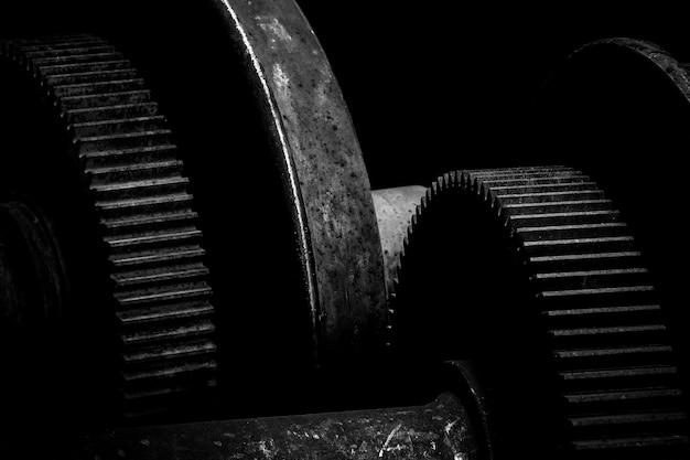 Engrenage en métal rouillé dans le fond sombre - monochrome Photo Premium