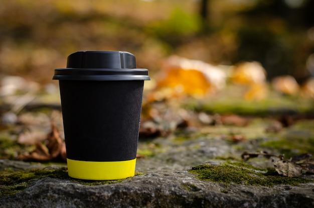 Enlevez la tasse à café noire avec couvercle à l'extérieur sur fond de feuilles mortes. espace de copie, maquette Photo Premium