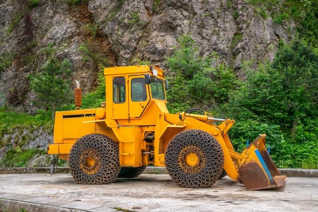 Un énorme bulldozer attend le temps de neige sur le chantier. Photo Premium