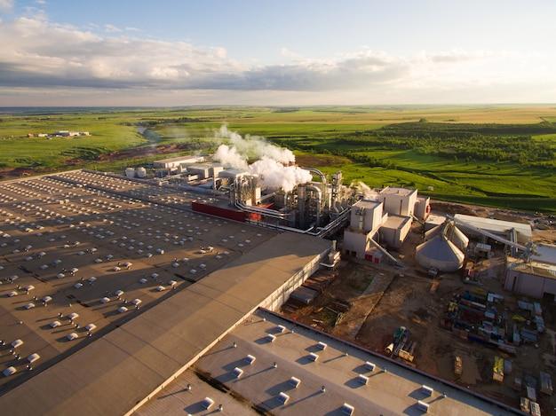 Énorme centrale à béton avec des tuyaux entre les champs. vue aérienne Photo Premium