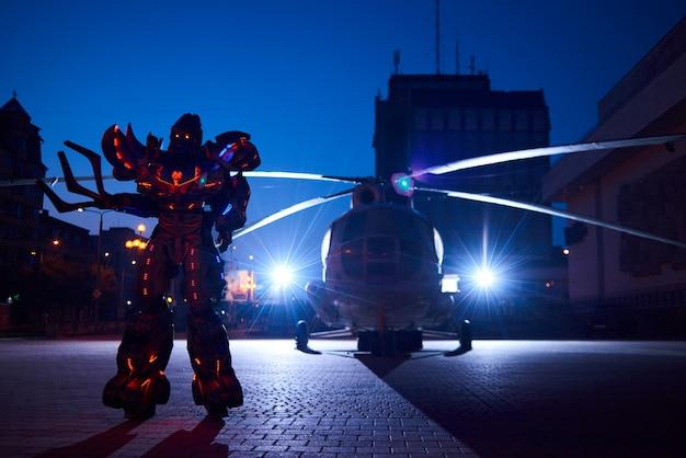 Énorme robot-transformateur debout devant la silhouette de l'hélicoptère militaire. Photo Premium