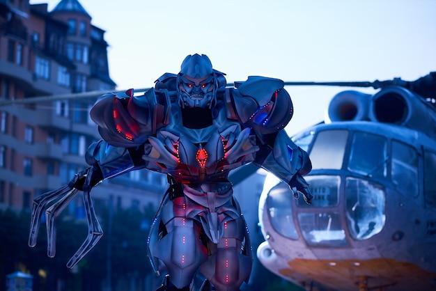 Énorme robot-transformateur se déplaçant à proximité d'un hélicoptère militaire dans le centre-ville. Photo Premium